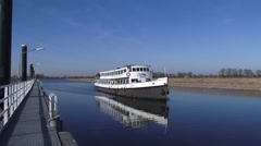 Party cruiser ship navigates on Maximakanaal along floating pier - side view Stock Footage