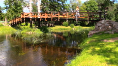 Woman in long dress walk bridge and reflections on river water Stock Footage