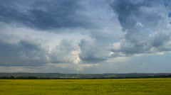 Moving cumulonimbus clouds over yellow field, time lapse. - stock footage