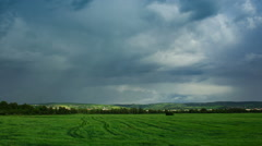 Moving cumulonimbus clouds over green field. Stock Footage