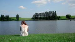 A girl sits by the river Stock Footage