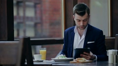 man dines with the tablet - stock footage