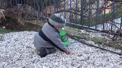 Baby collecting stones in to a bottle Stock Footage