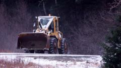 Loader on Blowing Snow Road Passed by Red Truck Stock Footage