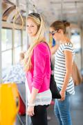 Pretty, young woman on a streetcar/tramway, during her commute t Stock Photos
