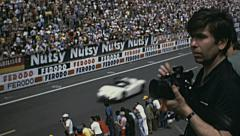 Le Mans 1972: people watching a vintage car race - stock footage