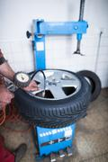 Auto mechanic in a garage checking the air pressure in a tyre wi Stock Photos