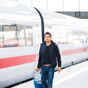 Just arrived: handsome young man walking along a platform at a m - stock photo