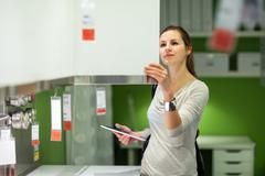 Young woman shopping for furniture in a furniture store, using h Stock Photos