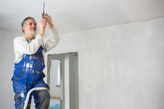 Senior man installing a bulb in a freshly renovated appartment i - stock photo