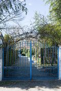 Metal wrought-iron gate and a house with landscaping Stock Photos
