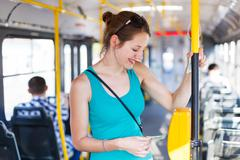 Pretty, young woman on a streetcar/tramway, during her commute t - stock photo