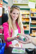 Beautiful young woman paying for her groceries at the counter of - stock photo