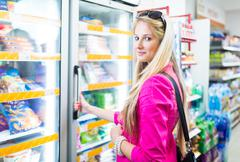 Beautiful young woman shopping in a grocery store/supermarket (c Kuvituskuvat