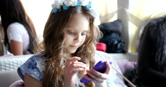 Beautiful school age girl typing her smartphone Stock Footage