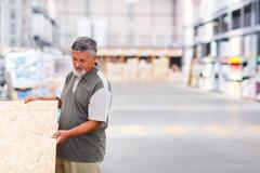 Senior man buying construction wood in a  DIY store - stock photo