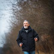 Senior man nordic walking, enjoying the outdoors Stock Photos