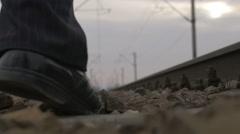 Man walks along railroad tracks - stock footage