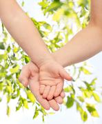 Close up of woman and little child hands together Stock Photos