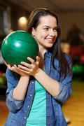 Stock Photo of happy young woman holding ball in bowling club