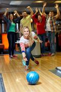 Stock Photo of happy young woman throwing ball in bowling club