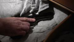 Hand reaching for handgun in drawer Stock Footage