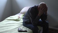 Hand gun on bed next to senior man Stock Footage