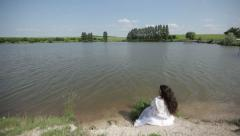 The girl is sitting near the lake (FLAT COLOR) Stock Footage