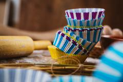 Colorful cupcake wrappers with baking pan on wooden background Stock Photos
