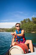 Handsome young man on a canoe on a lake, paddling, enjoying a lo Kuvituskuvat