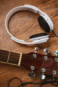 acoustic guitar and headphone on fabric sofa - stock photo