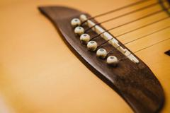Macro shot down the fretboard of acoustic guitar with shallow depth of field Stock Photos