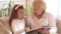 Grandmother reading a book with her granddaughter Stock Footage