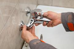 Plumber works in a bathroom - stock photo