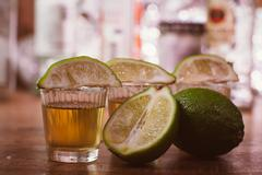 Tequila , lime and salt on wooden table Stock Photos