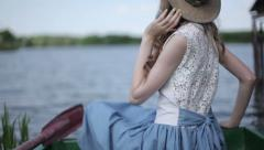 A girl sits in a boat  (FLAT COLOR) Stock Footage