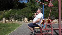 A big man with sunglasses talks on smartphone in outdoor gym MRL Stock Footage
