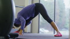 Flexible young woman stretching her hamstrings - stock footage