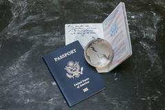 Two US passports and small glass globe on black background - stock photo