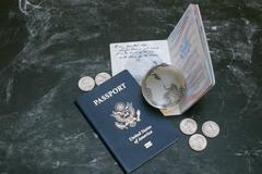 Two US passports, small glass globe and coins on black background - stock photo