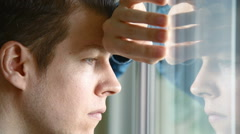 Unhappy man looking out of window Stock Footage