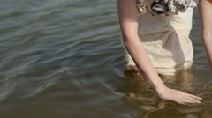 Girl dabbles in the river Stock Footage