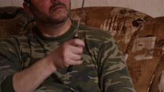Man in camouflage sharpening knifes on sofa Stock Footage