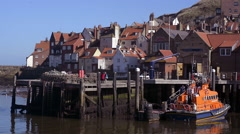 Lifeboat and houses Whitby harbour North Yorkshire - stock footage