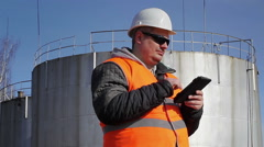 Engineer working with tablet PC near oil tank Stock Footage