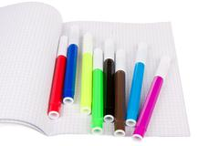 Exercise book with felt-pens isolated over white - stock photo