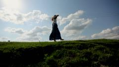 Girl in the hat jumping on the meadow Stock Footage