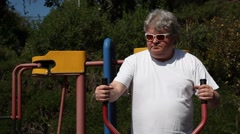 A big man with sunglasses works out in outdoor gym MRL Stock Footage