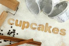 """Stencil word """"cupcakes"""" made with flour on wooden table - stock photo"""