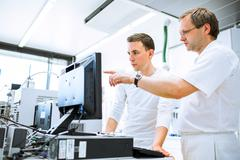 Team of researchers carrying out experiments in a lab (shallow D - stock photo